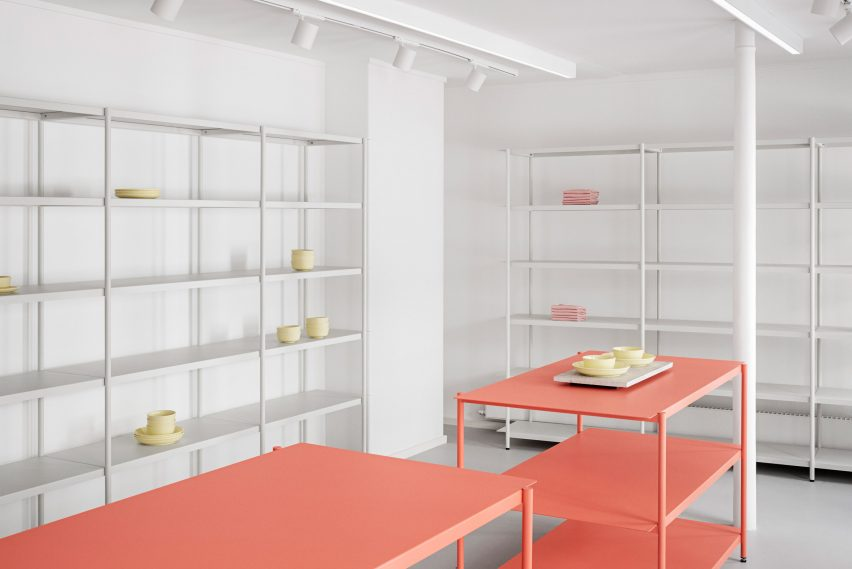 White and coral-coloured steel shelving in the OCE Copenhagen store interior