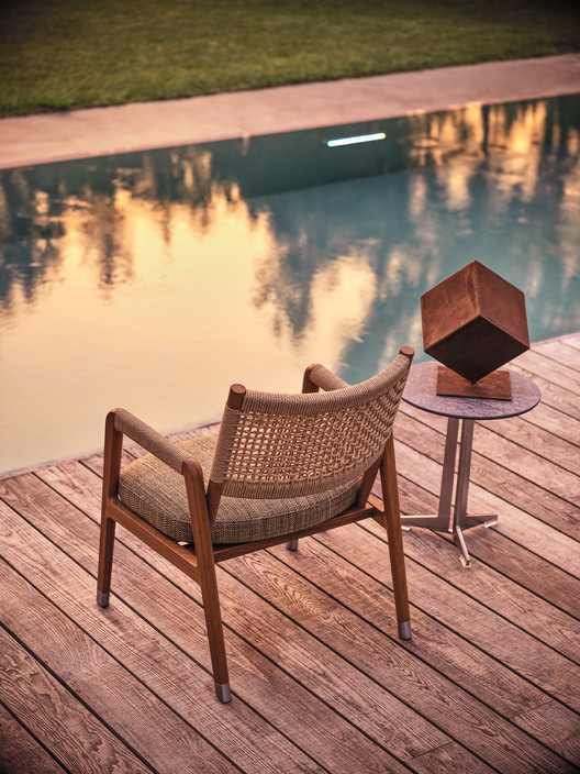 The Ortigia Outdoor armchairs offer practical comfort poolside. Image Courtesy of Flexform