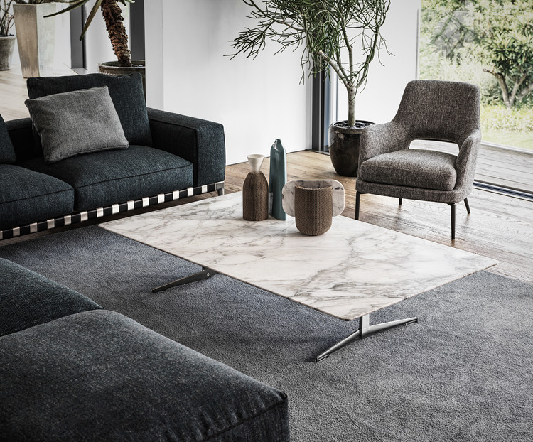 In the living room, a Gregory Sofa and a Joyce Armchair are paired with a veined marble Fly Coffee Table. Image Courtesy of Flexform