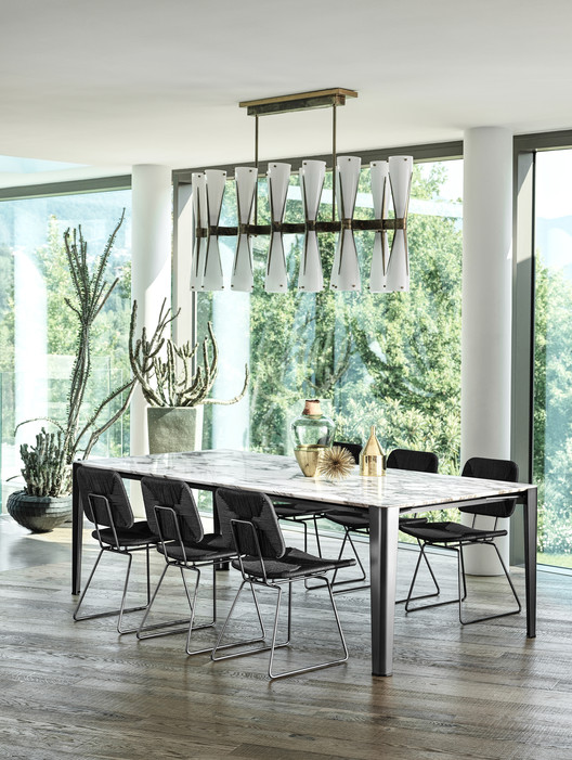 The Iseo dining table and Echoes dining chairs fit effortlessly into the lush surroundings. Image Courtesy of Flexform