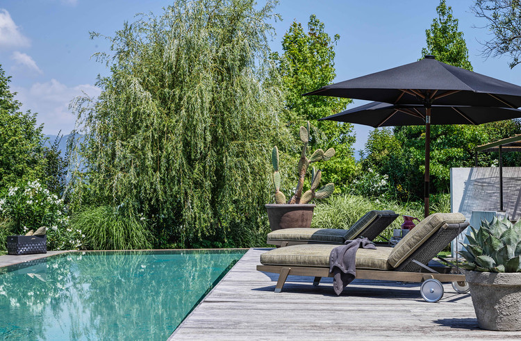 By the pool, two Hora Sexta daybeds form a cozy relaxation area. Image Courtesy of Flexform