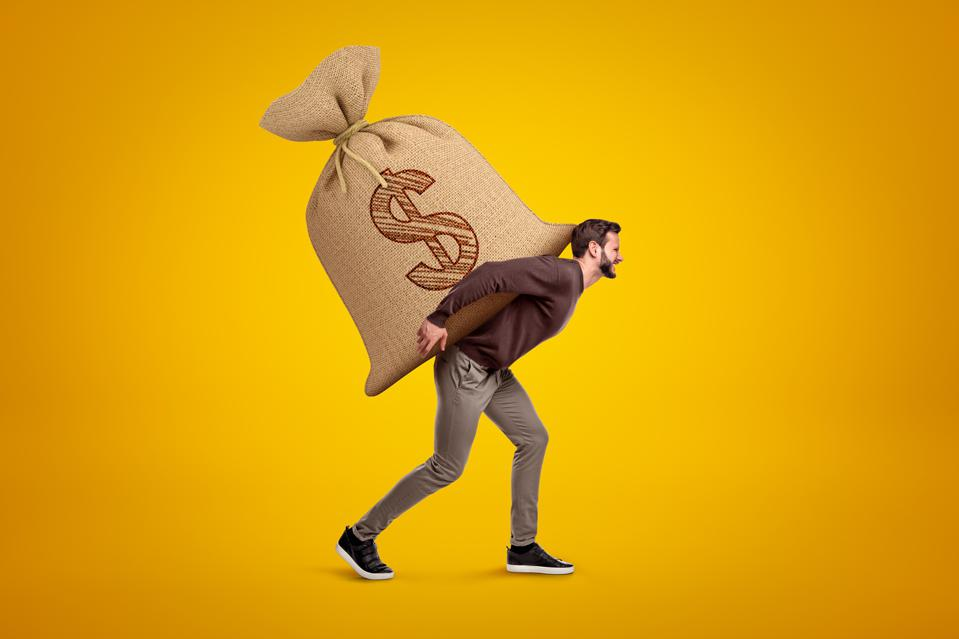 Side view of young handsome man in casual clothes carrying huge heavy sack with dollar symbol on.