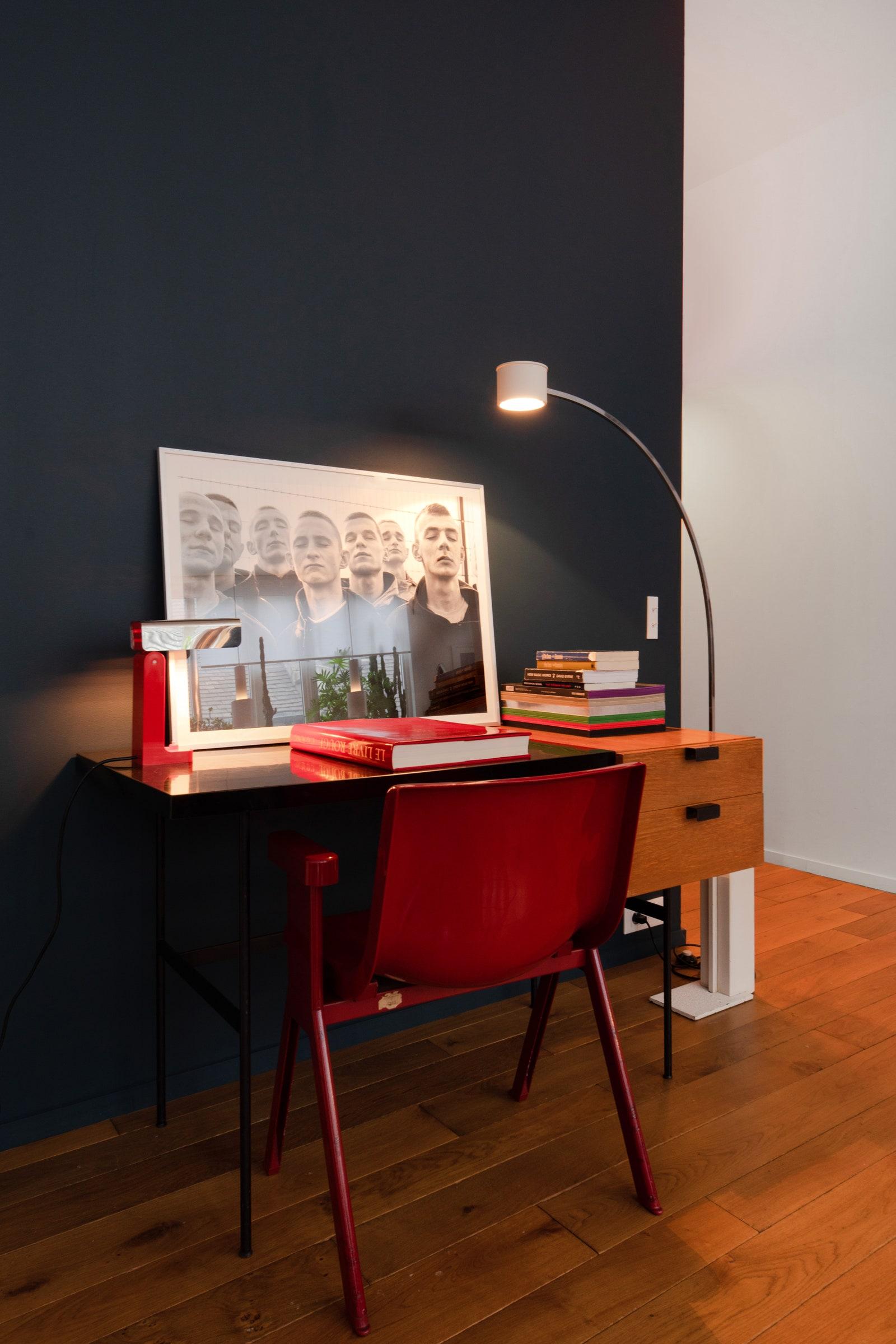 AZuza Krajewska photograph oftroubled teens rests atop Yoann's Pierre Paulin desk.