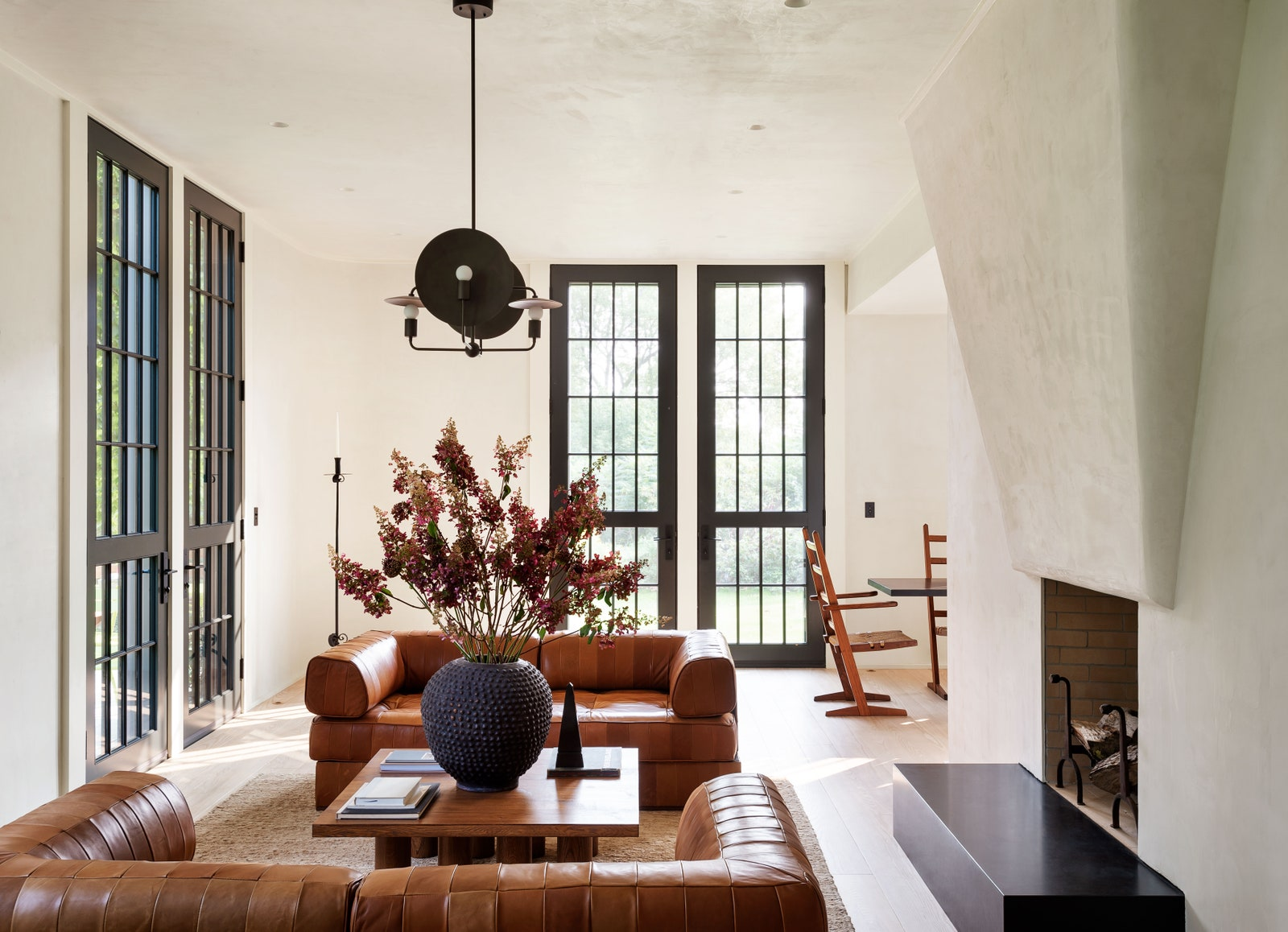 In the living room a pair of De Sede sofas are centered on a Nathan Lindberg cocktail table with a Workstead chandelier...