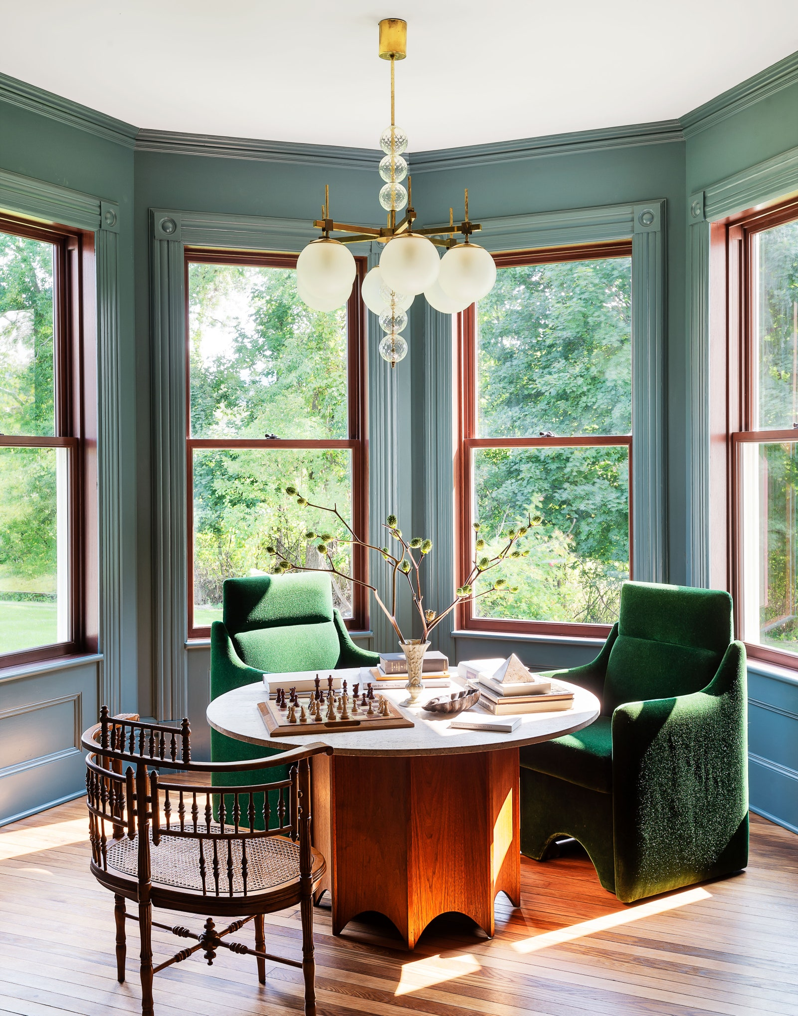 In the front parlor Luigi Caccia Dominioni chairs reupholstered in green mohair gather around a Harvey Probber games table.