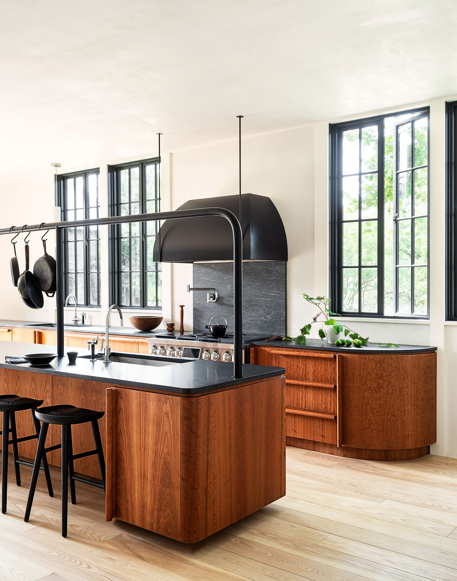Rejuvenation counter stools tuck into the custom cherryandgranite island which also features a custom pot rack...