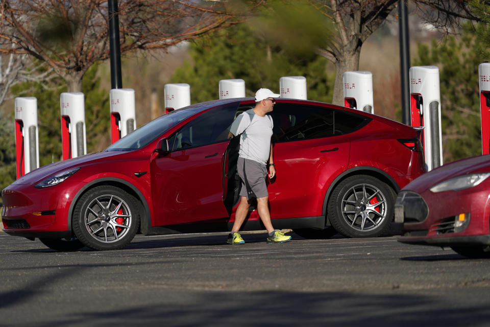 A motorist charges a 2020 Model Y at a Tesla supercharging station located in the parking lot of Colorado Mills outlet mall Wednesday, Nov. 17, 2020, in Golden, Colo. (AP Photo/David Zalubowski)
